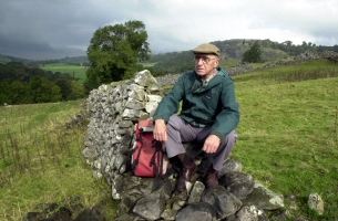 Bill Mitchell sitting on a drystone wall